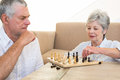 Senior couple sitting on floor playing chess at home in living room Royalty Free Stock Photography