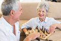 Senior couple sitting on floor playing chess at home in living room Royalty Free Stock Image