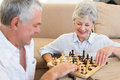 Senior couple sitting on floor playing chess at home in living room Stock Photo