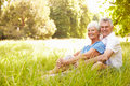 Senior couple sitting on grass together relaxing Royalty Free Stock Photo
