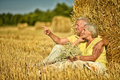Senior couple sitting near stack of hay Royalty Free Stock Photo