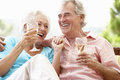 Senior Couple Sitting On Outdoor Seat Together Drinking Wine Royalty Free Stock Photo