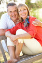 Senior Couple Sitting Outdoors On Bench Royalty Free Stock Photo