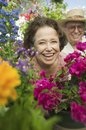 Senior couple sitting in plant nursery seen through bed of flowers portrait Royalty Free Stock Images