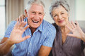 Senior couple sitting on sofa and smiling portrait of in living room Royalty Free Stock Photos