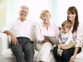 Senior couple sitting with their daughter and grandson smiling at home playing on a digital tablet Royalty Free Stock Images