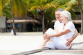 Senior couple sitting on wooden jetty smiling Royalty Free Stock Images