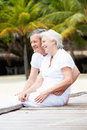 Senior couple sitting on wooden jetty smiling Stock Photo