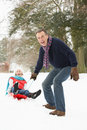 Senior Couple Sledging Through Snowy Woodland Royalty Free Stock Images
