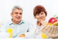 Senior couple smile having breakfast fruit orange juice sitting at table home kitchen Stock Photo