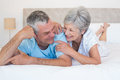 Senior couple smiling together on bed happy while lying at home Royalty Free Stock Photo