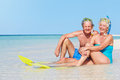 Senior couple snorkels enjoying beach holiday smiling Stock Photos