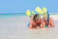 Senior couple snorkels enjoying beach holiday smiling Stock Image
