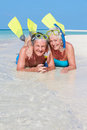 Senior couple snorkels enjoying beach holiday smiling Royalty Free Stock Images