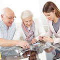 Senior couple solving jigsaw puzzle together with family at home Royalty Free Stock Photo