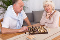 Senior couple spending evening together elderly happy playing chess at home Royalty Free Stock Photos