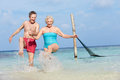 Senior couple splashing in beautiful tropical sea having fun Stock Images