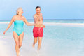 Senior couple splashing in beautiful tropical sea smiling Stock Photos