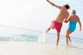 Senior couple splashing in sea on beach holiday having fun Royalty Free Stock Photography