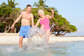Senior couple splashing in sea on tropical beach holiday having fun Stock Images