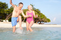 Senior couple splashing in sea on tropical beach holiday portrait of smiling to camera Stock Photography
