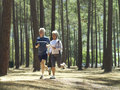 Senior couple in sportswear jogging through woodland smiling Royalty Free Stock Images