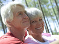 Senior couple in sportswear sitting in wood man embracing woman smiling close up portrait men Stock Photo