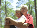 Senior couple in sportswear sitting in wood man embracing woman smiling low angle view men Royalty Free Stock Photos