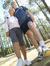 Senior couple in sportswear standing in clearing in wood smiling low angle view tilt Stock Photography