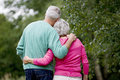 A senior couple standing with arms around each other rear view Stock Photography