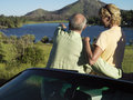 Senior couple standing beside convertible car man pointing at view of lake rear view men Royalty Free Stock Images