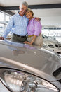Senior couple standing beside new car in showroom arms around each other smiling portrait Stock Photo