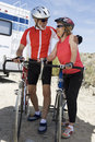 Senior Couple Standing By Their Bicycles And Looking At Each Other Stock Images