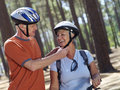 Senior couple standing in wood man adjusting strap on woman s cycling helmet smiling tilt men Stock Photography