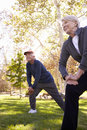 Senior Couple Stretching Whilst Exercising Together In Park Royalty Free Stock Photo