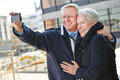 Senior couple taking pictures happy of themselves with a smartphone Royalty Free Stock Image