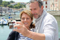 Senior couple taking selfie while travelling picture of themselves in touristic city Royalty Free Stock Photography