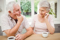 Senior couple talking to each other while having coffee in kitchen Stock Photography