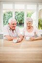 Senior couple talking to each other while having coffee in kitchen Royalty Free Stock Photos