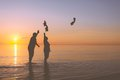Senior couple throws shoes on the beach Royalty Free Stock Images