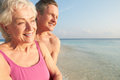 Senior couple on tropical beach holiday portrait of smiling to camera Stock Photos