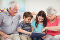 Senior couple using digital tablet with their grand children and in living room Stock Image