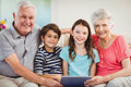 Senior couple using digital tablet with their grand children portrait of and in living room Royalty Free Stock Images