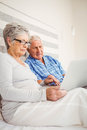 Senior couple using laptop in bedroom Stock Image