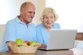 Senior couple using laptop at home two smiling people active eating fruits and enjoying modern technology computer with wireless Royalty Free Stock Image
