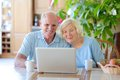 Senior couple using laptop at home two smiling people active eating fruits and enjoying modern technology computer with wireless Stock Images