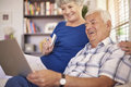 Senior couple using laptop internet helps us to pay our bills Royalty Free Stock Photo