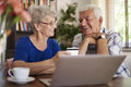Senior couple using laptop it is never too late to use some technology Royalty Free Stock Photo
