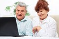 Senior couple using laptop sitting sofa smile on living room Stock Images
