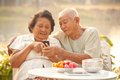 Senior couple using the mobile phone happy asian on outdoor background Royalty Free Stock Photos